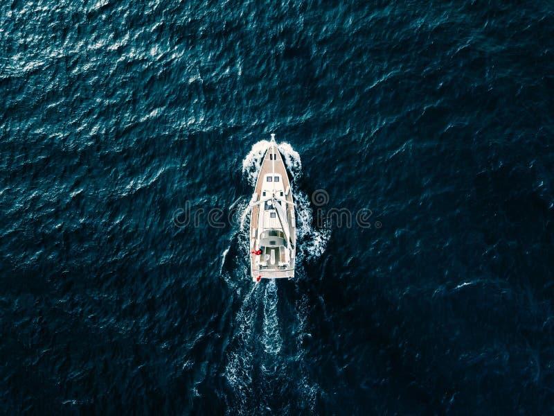 Εναέρια άποψη των πλέοντας γιοτ σκαφών με τα άσπρα πανιά στη βαθιά μπλε θάλασσα στοκ φωτογραφία με δικαίωμα ελεύθερης χρήσης