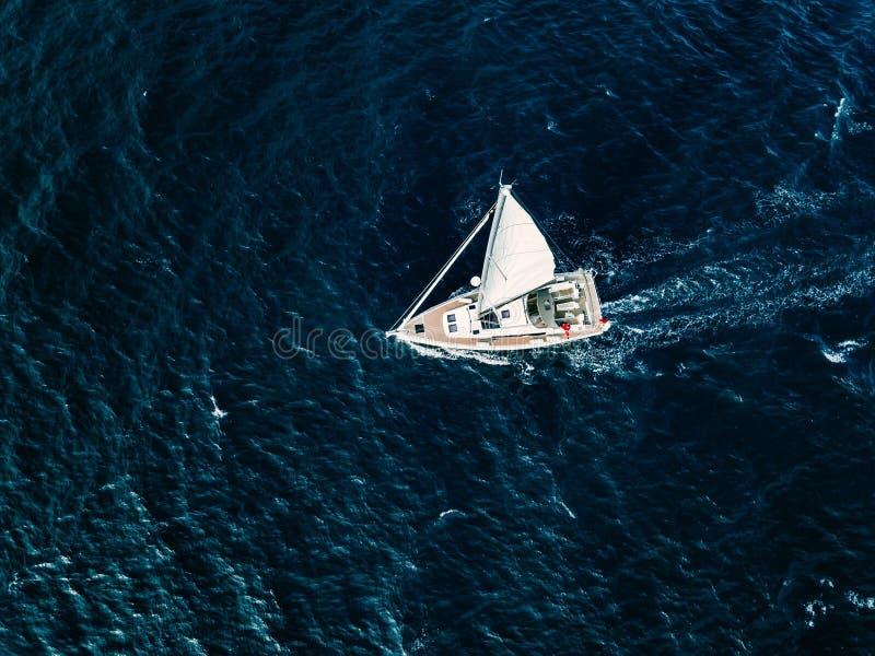 Εναέρια άποψη των πλέοντας γιοτ σκαφών με τα άσπρα πανιά στη βαθιά μπλε θάλασσα στοκ εικόνες