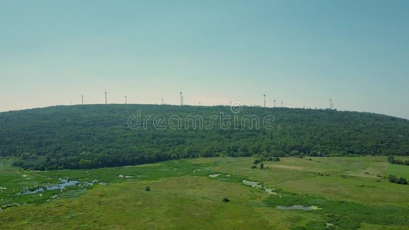 Εναέρια άποψη των πολλαπλάσιων γεννητριών αέρα επάνω από τη δασική πράσινη έννοια ενεργειακής παραγωγής στοκ εικόνες