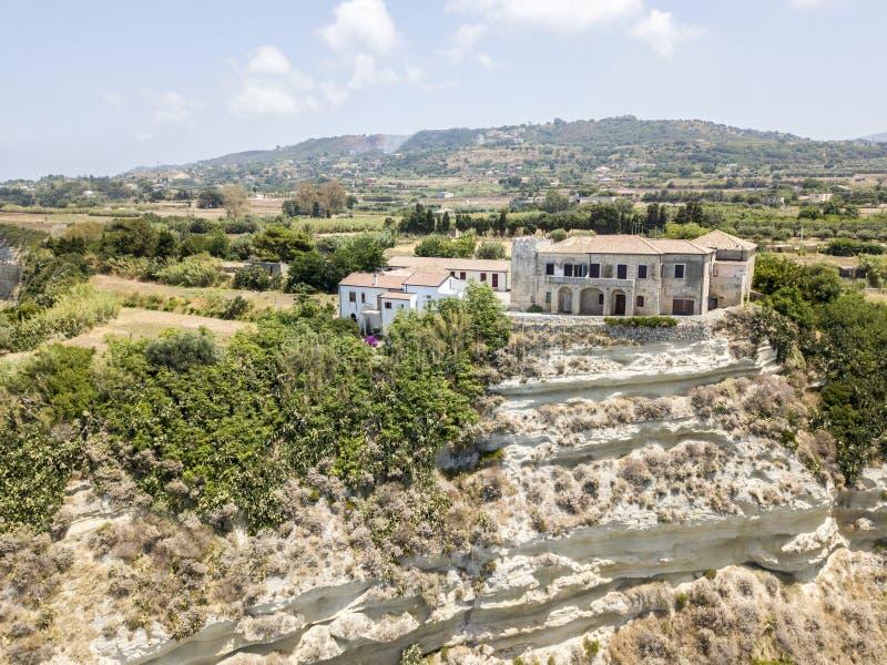 Εναέρια άποψη των σπιτιών στο βράχο πέρα από έναν ακρωτήριο που αγνοεί τη θάλασσα, Ricadi, Capo Vaticano, Καλαβρία στοκ εικόνες