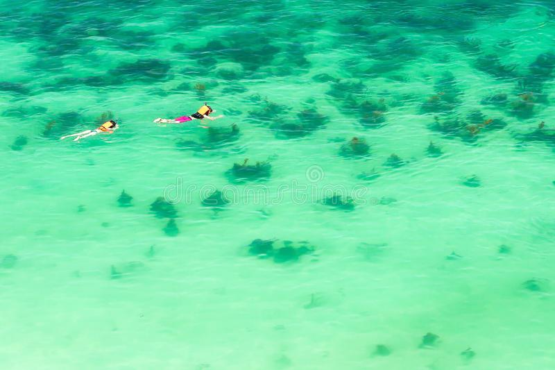 Εναέρια άποψη των τουριστών ζευγών που κολυμπούν με αναπνευτήρα στο νερό της θάλασσας κρυστάλλου, φωτεινό θερινό πρωί στοκ φωτογραφίες