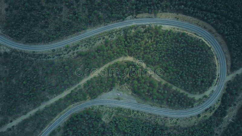 Εναέρια από επάνω προς τα κάτω άποψη ενός άσπρου αυτοκινήτου που σταθμεύουν στο θυελλώδη δρόμο στα βουνά στοκ εικόνα με δικαίωμα ελεύθερης χρήσης