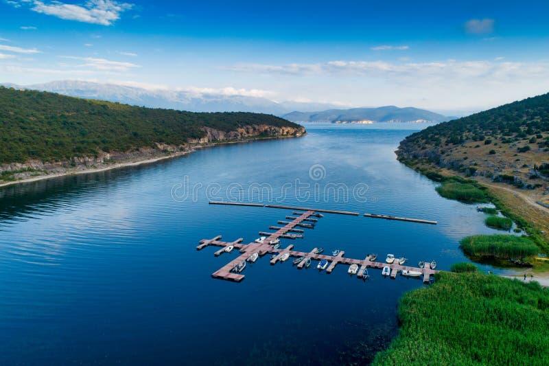 Εναέρια εικόνα της επιπλέουσας αποβάθρας με τις βάρκες, motorboats και τα σκάφη που επιπλέουν στο νερό στη λίμνη μικρό Prespes στοκ φωτογραφία με δικαίωμα ελεύθερης χρήσης