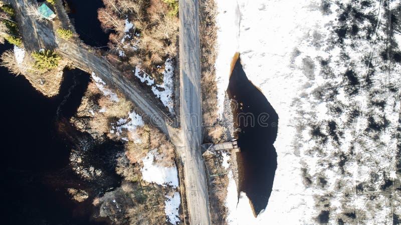 Εναέρια τοπ άποψη ενός δρόμου κλάδων, ενός άσπρων χιονωδών εδάφους και του δρόμου, δέντρα στοκ φωτογραφία