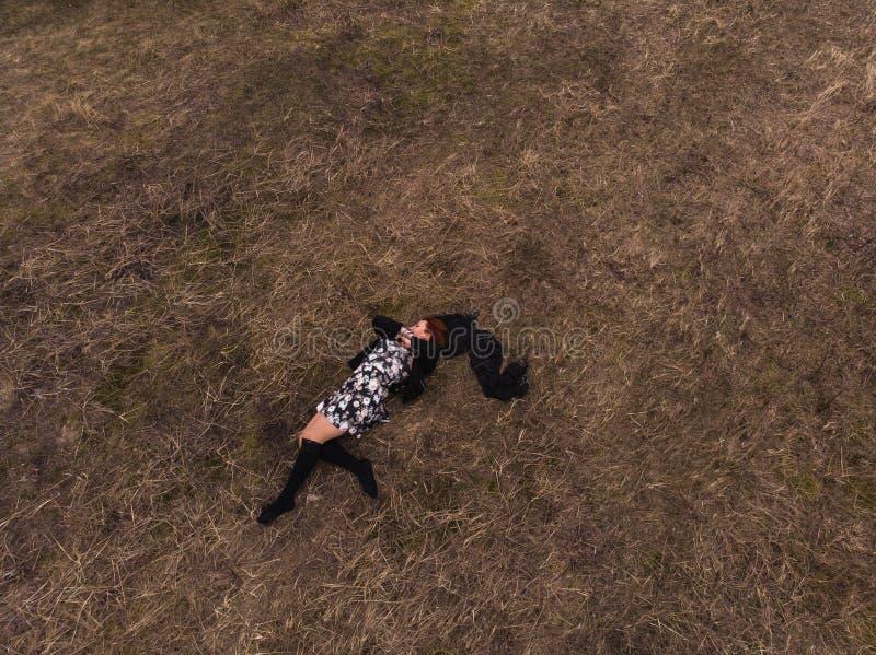 Εναέρια τοπ άποψη κηφήνων ενός κοριτσιού που βρίσκεται σε έναν τομέα που χαλαρώνει και που χορεύει Φθορά ενός φορέματος με τις γυ στοκ φωτογραφία με δικαίωμα ελεύθερης χρήσης