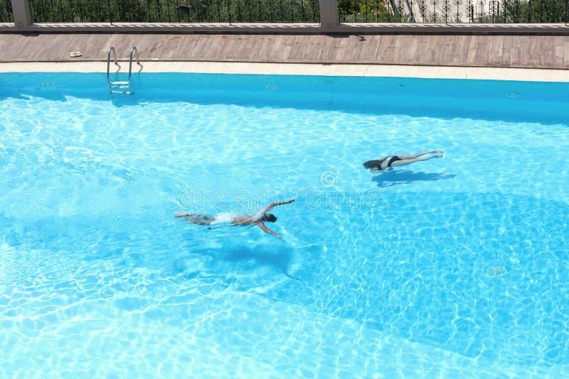 Εναέρια τοπ άποψη σχετικά με τους άνδρες και τη γυναίκα στην πισίνα με το διαφανές μπλε νερό στοκ εικόνες