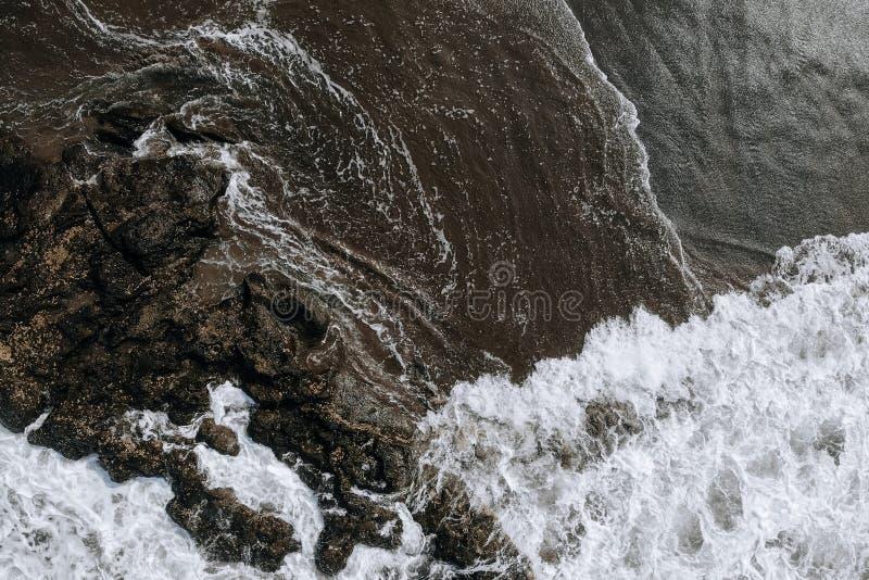 Εναέρια φωτογραφία τοπ άποψης από τον πετώντας κηφήνα του ωκεάνιου τοπίου με τα μεγάλους κύματα και τους βράχους στη μαύρη παραλί στοκ εικόνες με δικαίωμα ελεύθερης χρήσης