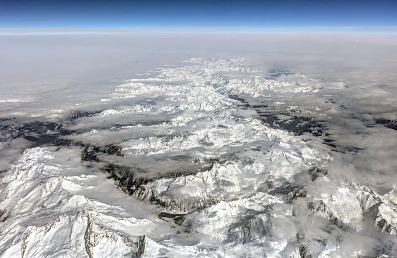 Εναέρια φωτογραφία HDR του τοπίου με τα σύννεφα, τα χιονώδη βουνά και την άποψη που τεντώνουν όλο τον τρόπο στον ορίζοντα στοκ φωτογραφία