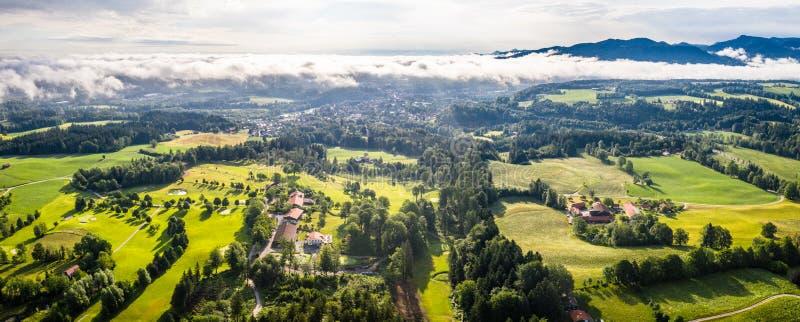 Εναέριες κακές βαυαρικές Άλπεις Toelz Γήπεδο του γκολφ Βουνό Blomberg Κηφήνας πρωινού που πυροβολείται με μερικά σύννεφα στον ουρ στοκ φωτογραφία με δικαίωμα ελεύθερης χρήσης