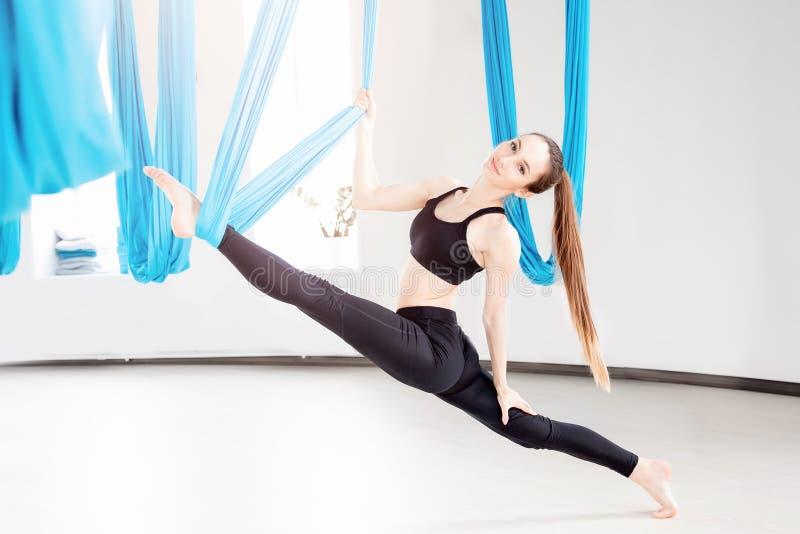 Εναέριος μυγών gymnast γυναικών γιόγκας νέος όμορφος στην μπλε αιώρα στοκ εικόνα με δικαίωμα ελεύθερης χρήσης