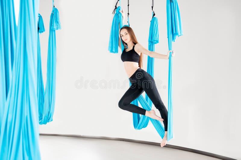 Εναέριος μυγών gymnast γυναικών γιόγκας νέος όμορφος στην μπλε αιώρα στοκ φωτογραφία με δικαίωμα ελεύθερης χρήσης