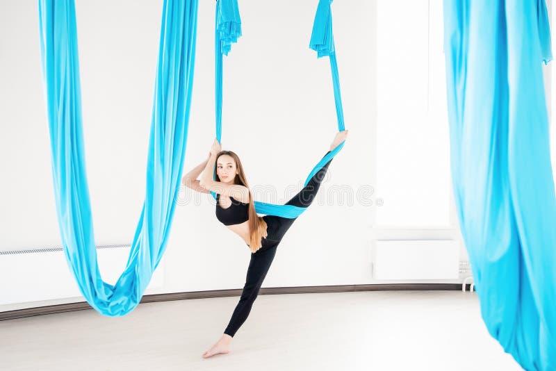 Εναέριος μυγών gymnast γυναικών γιόγκας νέος όμορφος στην μπλε αιώρα στοκ εικόνες με δικαίωμα ελεύθερης χρήσης