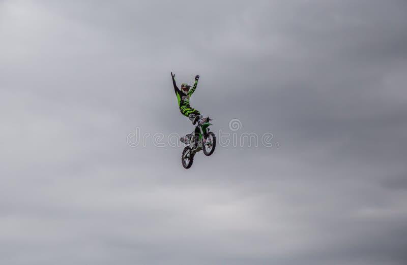 Εναέριος πυροβολισμός του αναβάτη ακροβατικής επίδειξης που στέκεται επάνω στον αέρα στο ποδήλατο ακροβατικής επίδειξής του ενάντ στοκ φωτογραφία με δικαίωμα ελεύθερης χρήσης