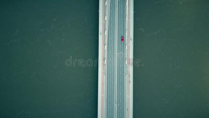 Εναέριος πυροβολισμός της γέφυρας καλωδίων με τους πεζούς, τα ποδήλατα και το κόκκινο αυτοκίνητο που διασχίζουν τον ποταμό, τοπ ά στοκ εικόνες
