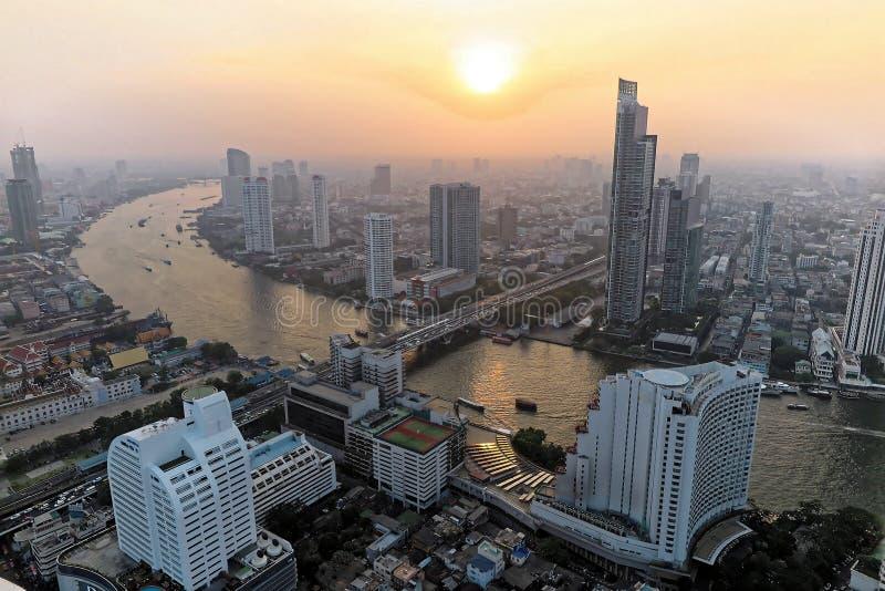 Εναέριο πανόραμα της Μπανγκόκ στο σούρουπο με την πολυάσχολη κυκλοφορία στη γέφυρα, τις βάρκες & τα πορθμεία Taksin στον ποταμό κ στοκ εικόνα