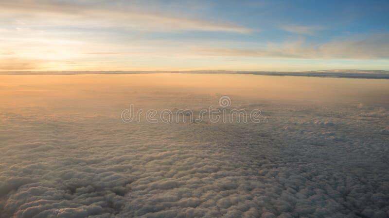Εναέριο ταξίδι Πέταγμα στο σούρουπο ή την αυγή Μύγα μέσω του πορτοκαλιών σύννεφου και του ήλιου στοκ εικόνα