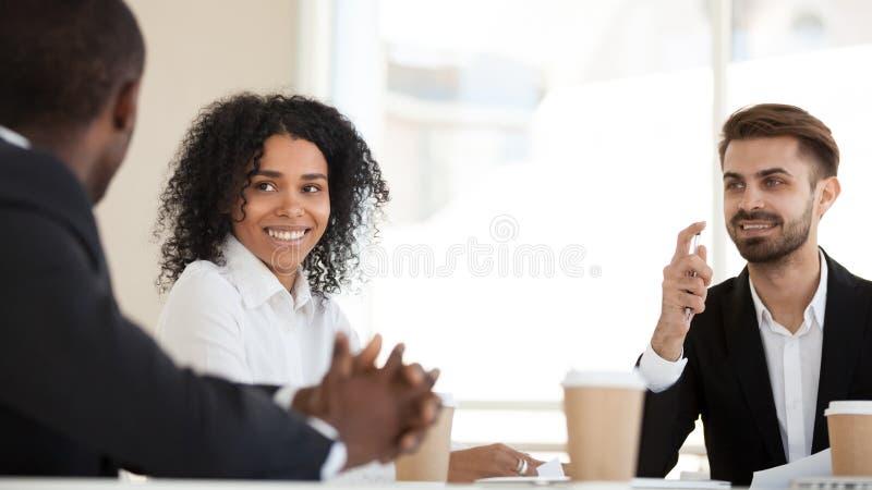 Ενδιαφερόμενοι διαφορετικοί υπάλληλοι που ακούνε τη συζήτηση συναδέλφων στην ενημέρωση στοκ φωτογραφία