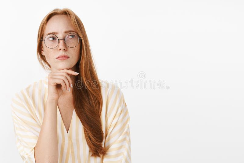 Ενδιαφερόμενος στοχαστικός και συγκεντρωμένος δημιουργικός θηλυκός συγγραφέας με την κόκκινη τρίχα και φακίδες στα γυαλιά και καθ στοκ εικόνες με δικαίωμα ελεύθερης χρήσης