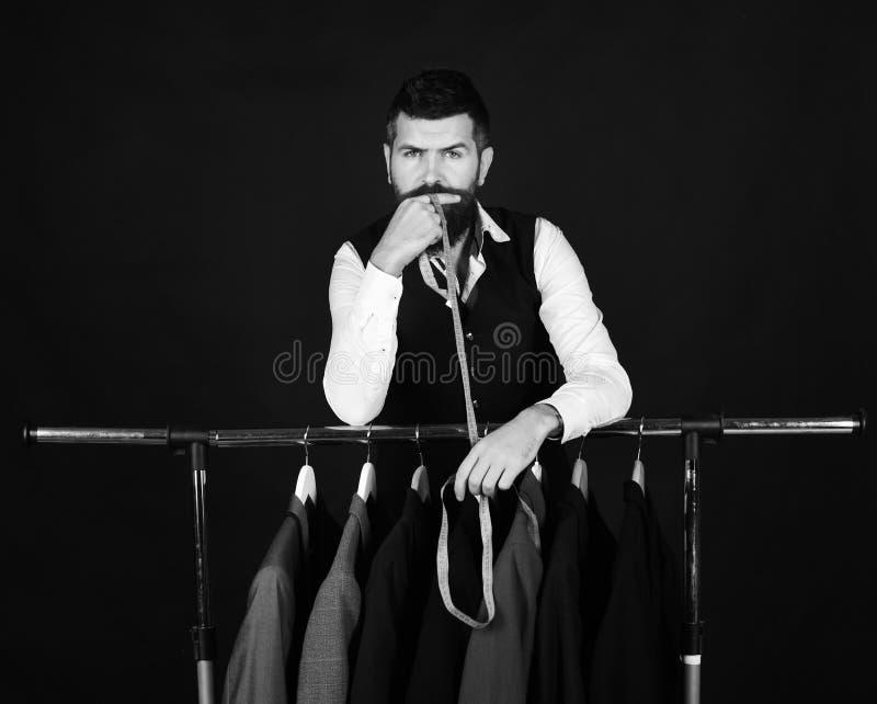 Ενδύματα μόδας Άτομο με τη γενειάδα από το ράφι ενδυμάτων Βοηθός ή πωλητής καταστημάτων στοκ φωτογραφία