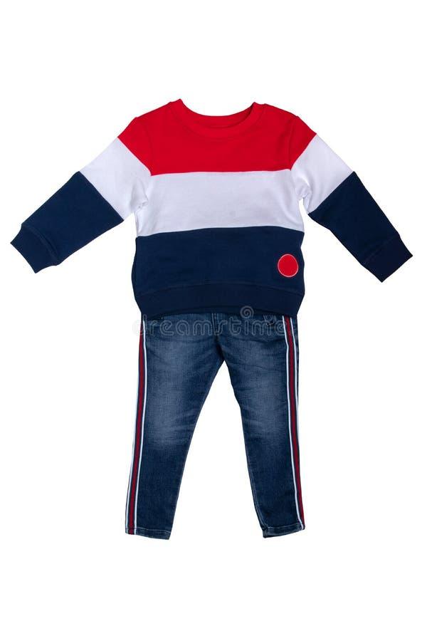 Ενδύματα παιδιών άνοιξης και φθινοπώρου Τζιν παντελόνι και ένα κόκκινο άσπρο μπλε ριγωτό άνετο θερμό πουλόβερ ή ένα πουλόβερ που  στοκ φωτογραφία