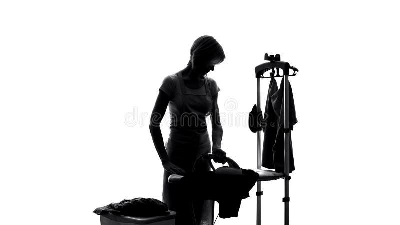 Ενδύματα πελατών σιδερώματος εργαζομένων υπηρεσιών πλυντηρίων, στεγνός καθαρισμός ξενοδοχείων, νοικοκυρά στοκ εικόνες