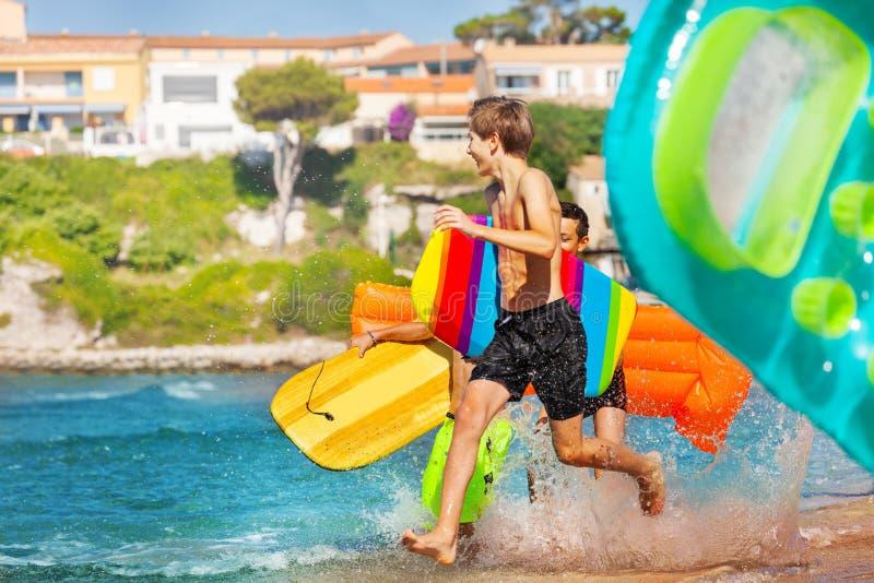 Ενεργά αγόρια που τρέχουν στη θάλασσα με τους πίνακες σωμάτων στοκ φωτογραφίες με δικαίωμα ελεύθερης χρήσης