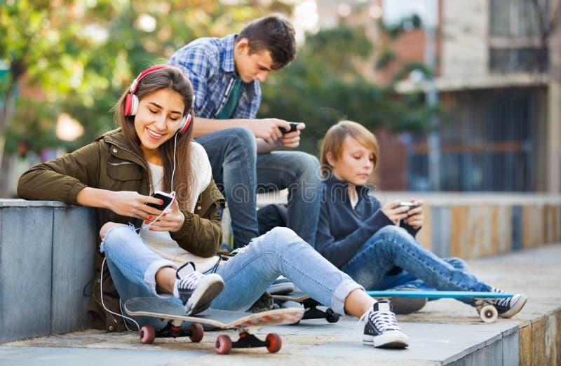 Ενεργά teens που παίζουν στα smarthphones και που ακούνε τη μουσική στοκ εικόνα