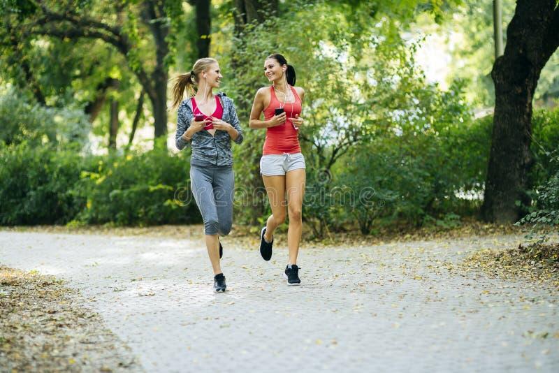 Ενεργητικές νέες γυναίκες που τρέχουν υπαίθρια στοκ εικόνα