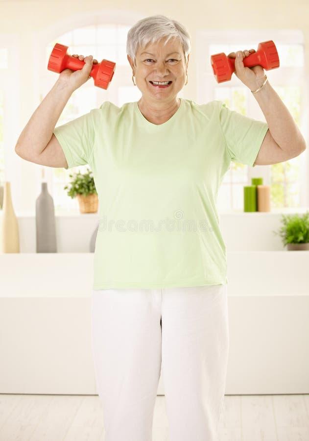 Ενεργητική ηλικιωμένη γυναίκα που εκπαιδεύει στο σπίτι στοκ εικόνες