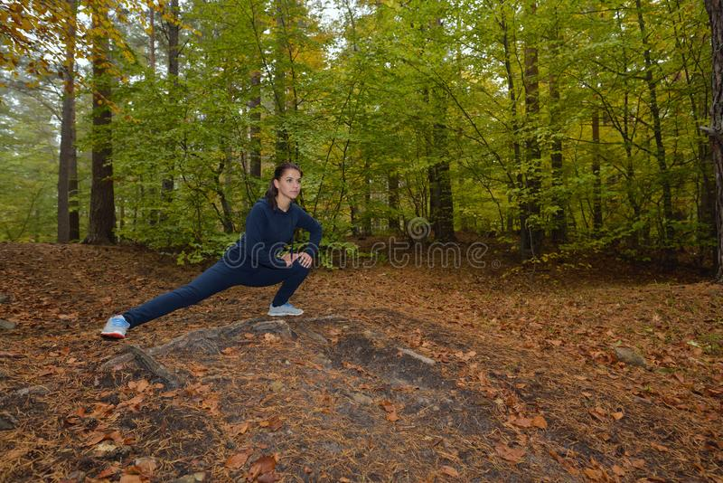 Ενεργητική νέα woman do exercises υπαίθρια στο πάρκο για να κρατήσει το thei στοκ εικόνα με δικαίωμα ελεύθερης χρήσης