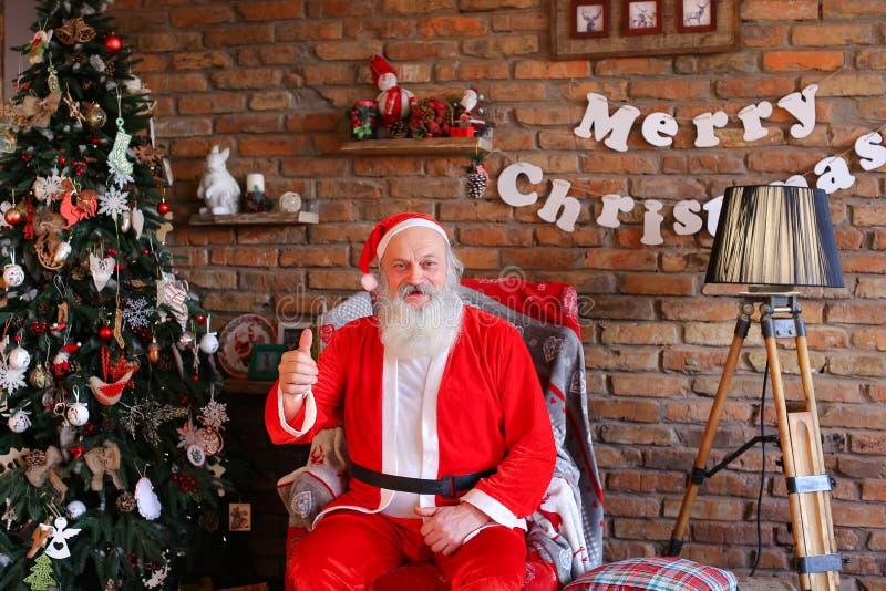 Ενεργητικός Άγιος Βασίλης αυξάνει τον αντίχειρα επάνω, καθμένος στην πολυθρόνα στο Φε στοκ εικόνα με δικαίωμα ελεύθερης χρήσης
