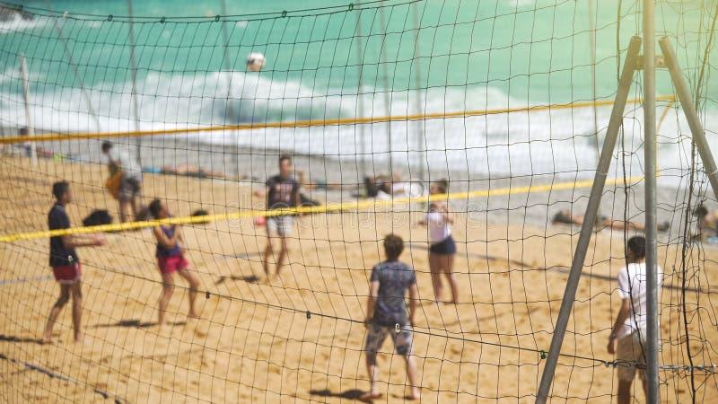 Ενεργοί νέοι που παίζουν την πετοσφαίριση στην αμμώδη παραλία, αθλητισμός ομάδων για τους φίλους στοκ εικόνα