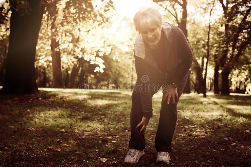 Ενεργός ανώτερη γυναίκα που έχει τον πόνο στο γόνατο μετά από την άσκηση στοκ φωτογραφία με δικαίωμα ελεύθερης χρήσης