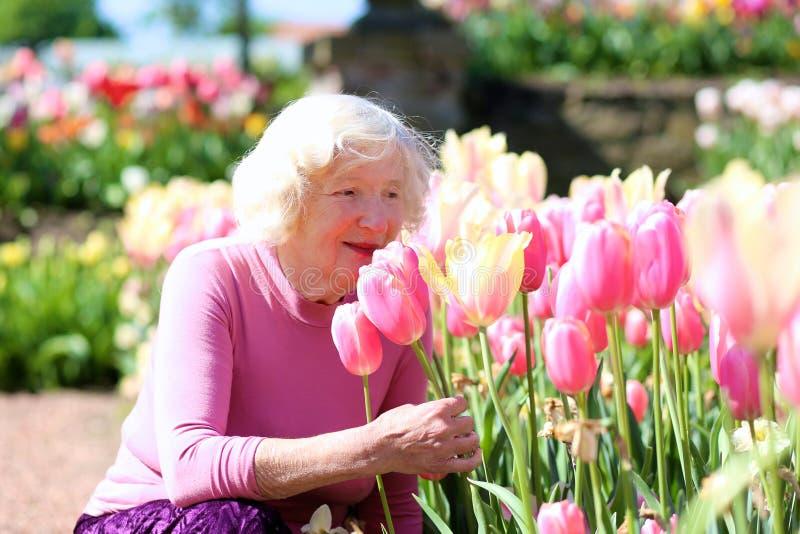Ενεργός ανώτερη γυναίκα που απολαμβάνει το πάρκο λουλουδιών στοκ εικόνες