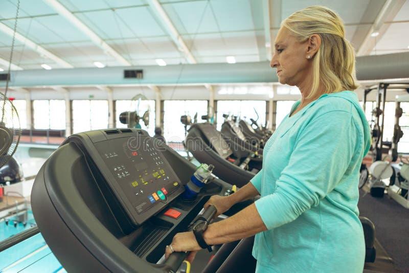 Ενεργός ανώτερη γυναίκα που ασκεί treadmill στο στούντιο ικανότητας στοκ εικόνες