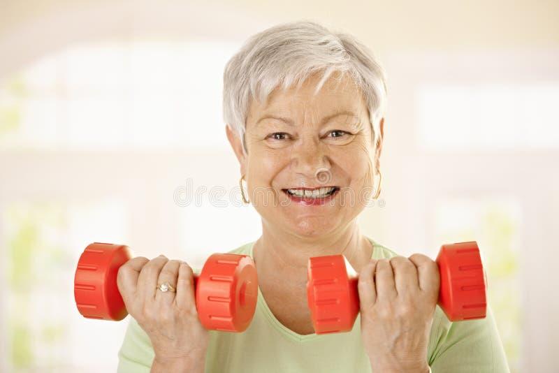 Ενεργός ανώτερη γυναίκα που κάνει τις ασκήσεις στοκ εικόνα
