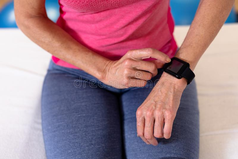 Ενεργός ανώτερη γυναίκα που χρησιμοποιεί smartwatch στο αθλητικό κέντρο στοκ φωτογραφίες