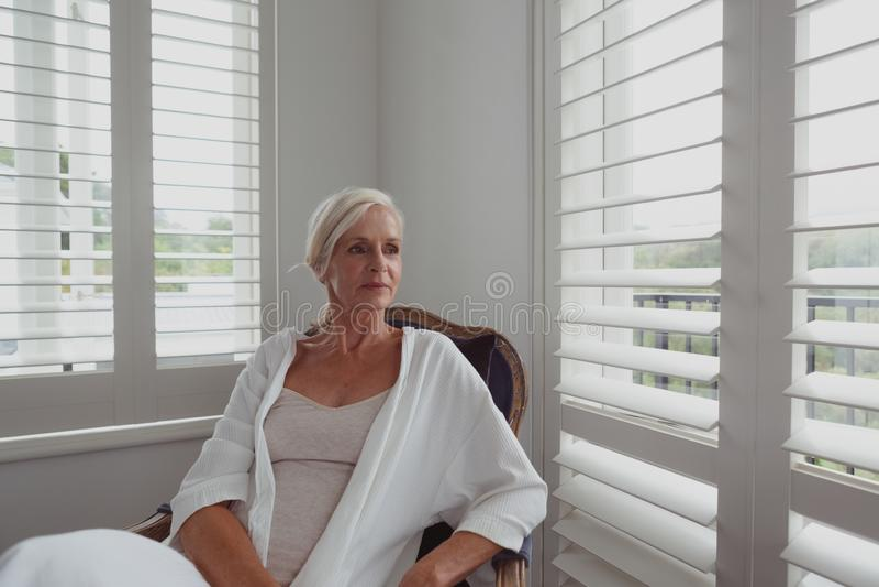 Ενεργός ανώτερη συνεδρίαση γυναικών στην καρέκλα σε ένα άνετο σπίτι στοκ εικόνες