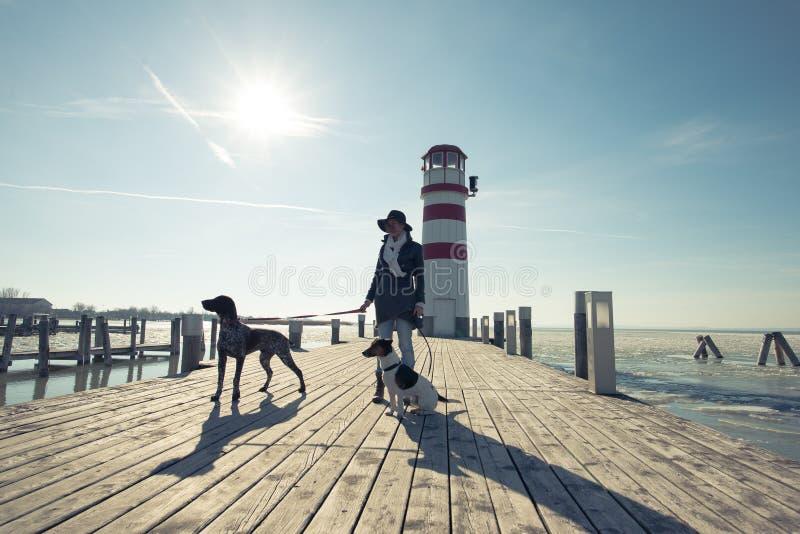 Ενεργός γυναίκα τρόπου ζωής με την τοποθέτηση σκυλιών υπαίθρια στοκ φωτογραφία