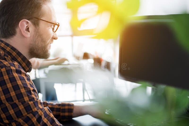 Ενεργός εργαζόμενος που χρησιμοποιεί τον υπολογιστή στην αρχή στοκ φωτογραφία