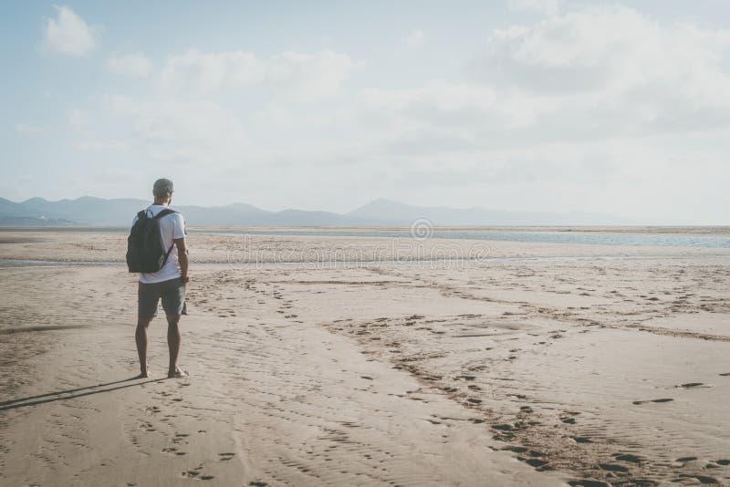Ενεργός μυϊκός γενειοφόρος αθλητής που στέκεται στην ακροθαλασσιά στην ανατολή με το σακίδιο πλάτης και που φαίνεται ορίζοντας στοκ φωτογραφία με δικαίωμα ελεύθερης χρήσης