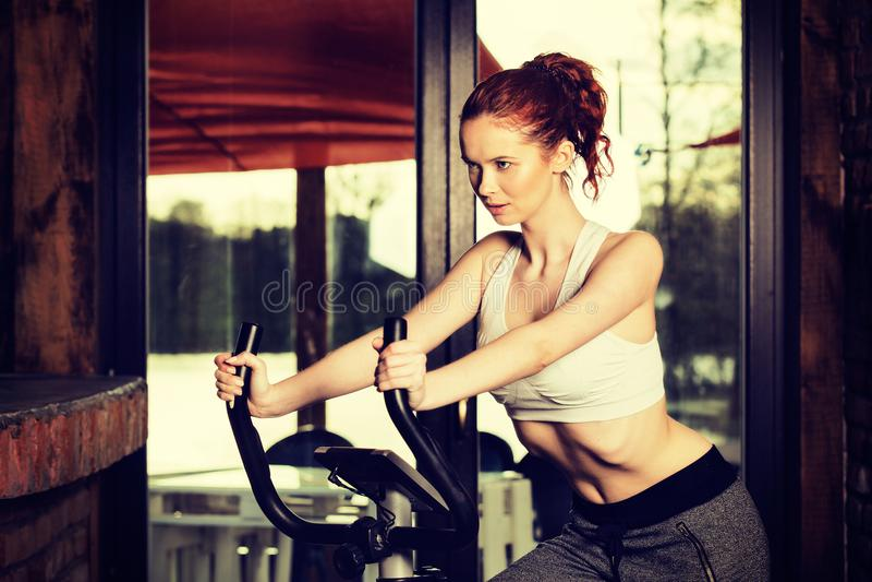Ενεργός νέα γυναίκα που κάνει την άσκηση στο ποδήλατο στο σπίτι στοκ εικόνα με δικαίωμα ελεύθερης χρήσης