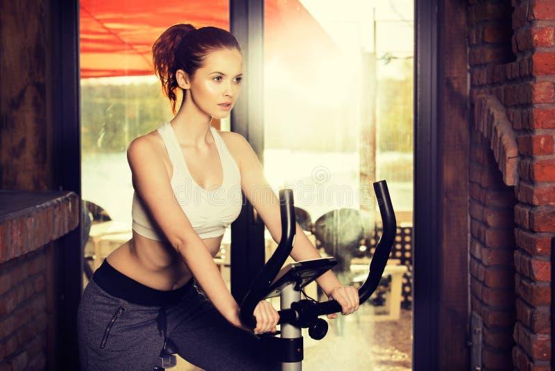 Ενεργός νέα γυναίκα που κάνει την άσκηση στο ποδήλατο στο σπίτι στοκ εικόνες με δικαίωμα ελεύθερης χρήσης