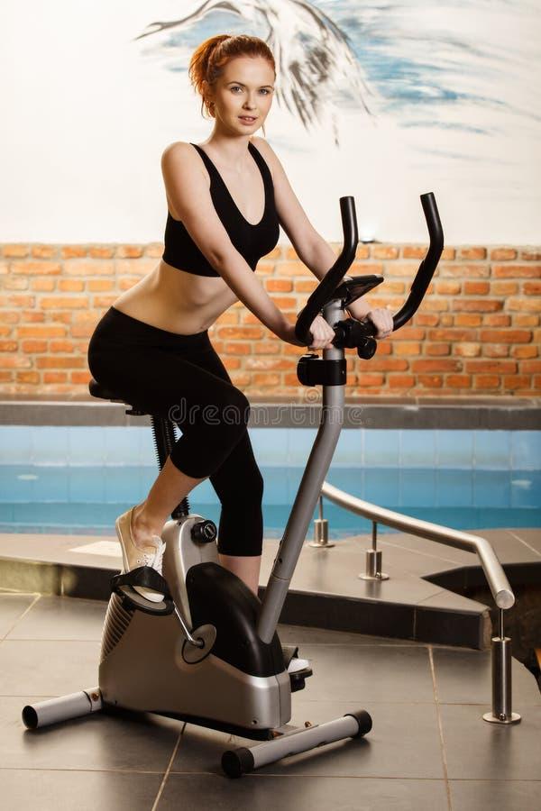 Ενεργός νέα γυναίκα που κάνει την άσκηση στο ποδήλατο στο σπίτι στοκ φωτογραφίες