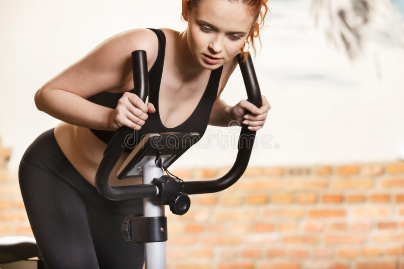 Ενεργός νέα γυναίκα που κάνει την άσκηση στο ποδήλατο στο σπίτι στοκ εικόνες