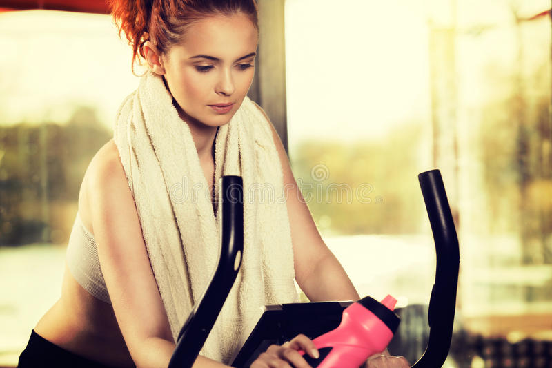 Ενεργός νέα γυναίκα που κάνει την άσκηση στο ποδήλατο στο σπίτι στοκ φωτογραφία