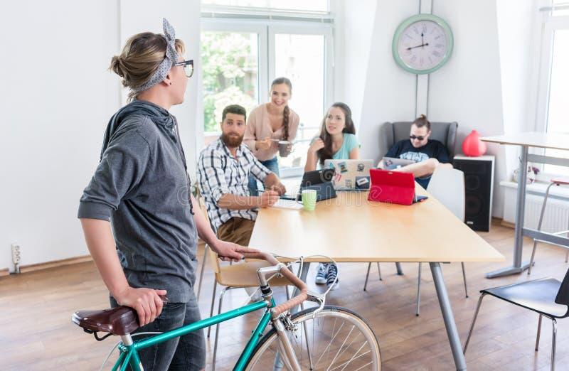 Ενεργός νέα γυναίκα που κρατά ένα ποδήλατο κατόχων διαρκούς εισιτήριου σύγχρονο κοινό σε έναν ομο στοκ εικόνες με δικαίωμα ελεύθερης χρήσης