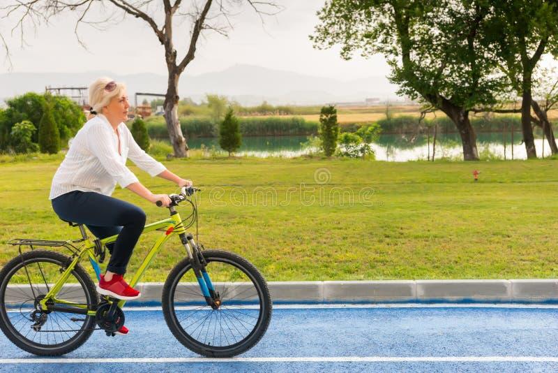 Ενεργός ξανθή γυναίκα που οδηγά ένα ποδήλατο στοκ εικόνες