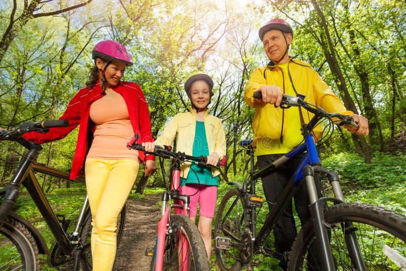 Ενεργός οικογένεια με τα ποδήλατα βουνών που περπατά στο πάρκο στοκ φωτογραφία