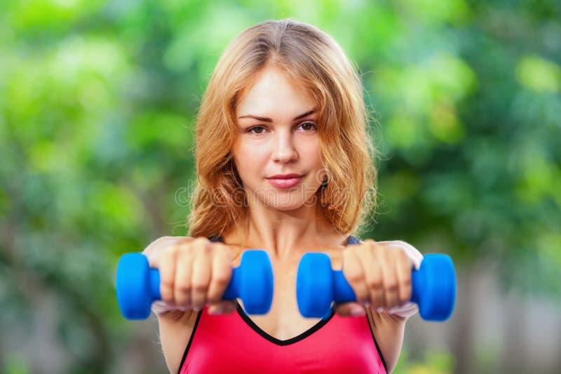 Ενεργός φίλαθλη γυναίκα που κάνει τις ασκήσεις πρωινού με τους αλτήρες στο σπίτι στοκ εικόνες